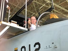 F15戦闘機で決めポーズの湯上会長